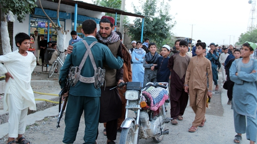 A Taliban militant embraces a member of the Afghan police, during a visit to greet people amid the three-day ceasefire