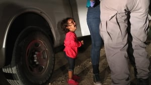 A two-year-old Honduran girl cries as her mother is searched and detained near the US-Mexico border