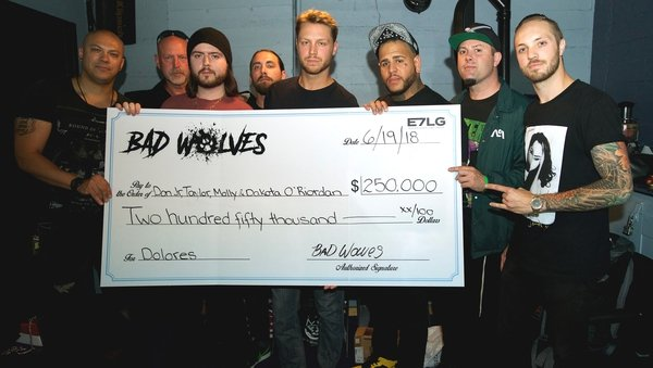 Dolores O'Riordan's children accept the cheque from Bad Wolves. L-R: Doc Coyle (Guitar), Don Burton, Taylor Burton, Kyle Konkiel (Bass), Don Burton Jr., Tommy Vext (Vocals), John Boecklin (Drums), Chris Cain (Guitar)