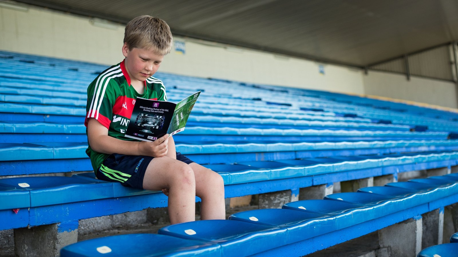 Image - A young fan reads the programme, but is it becoming a pointless endeavour?