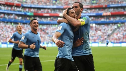 Diego Godin celebrates with Edinson Cavani while playing for Uruguay