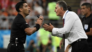 Referee Enrique Caceres has words with Iran's Portuguese coach Carlos Queiroz