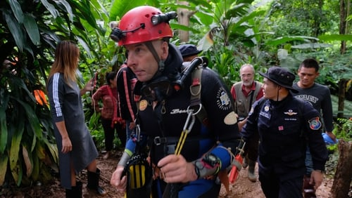 Divers with extra supplies advance in flooded cave passageway