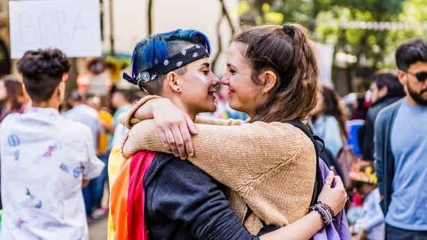 lgbtq+ couple embracing at pride parade