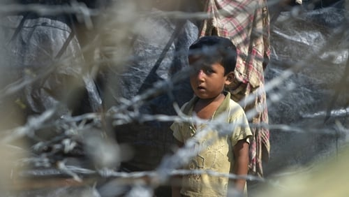 A child is seen behind a barbed wire fence in 'no man's land' at the border betweeen Myanmar and Bangladesh