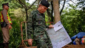 An officer carrying a map of the area walks out of Tham Luang Nang Non cave where the soccer team went missing