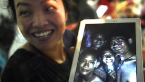 A family member shows a picture of four of the 12 trapped boys
