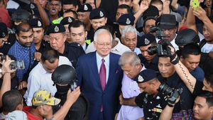 Najib Razak surrounded by police media and supporters outside court