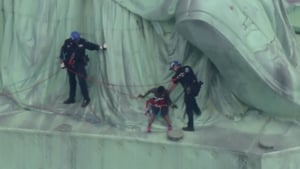 The woman accompanied police down off the monument after ther four-hour protest