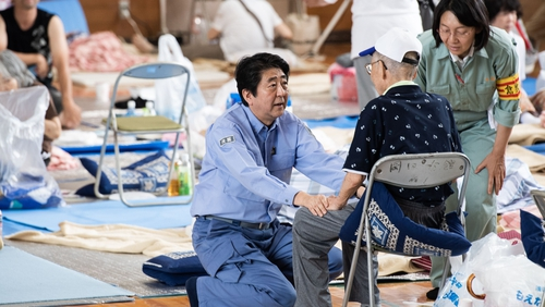 Shinzo Abe (C) visits a shelter for people affected by the recent flooding in Mabi, Okayama prefecture