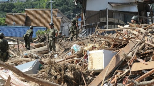 Rescue teams search for missing people at a flood damage site in Kure, Hiroshima