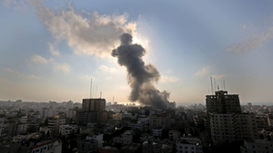 Smoke rises from a building in Gaza following fire from an Israeli fighter jet