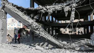 Palestinians walk among the wreckage of a building in Gaza following Israeli air strikes
