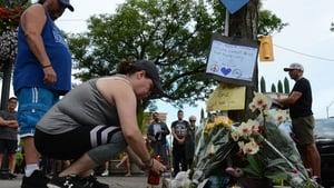 People in Toronto add flowers and messages to a memorial remembering the victims of the shooting