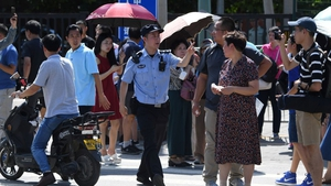 A Chinese police officer gestures among a crowd of bystanders gathered outside the US embassy in Beijing following a blast