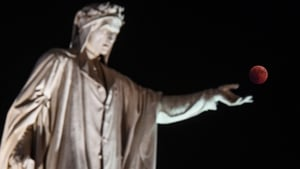 Statue of Dante Alighieri appears to reach out to the 'blood moon' in Naples