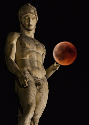 'Blood moon' eclipse beside a statue of ancient Greek god Ares in central Athens