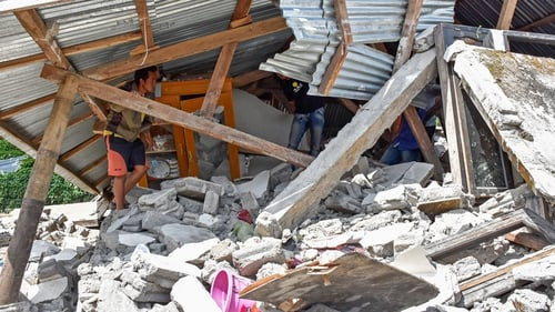 An Indonesian man looks at the remains of a house after the earthquake struck