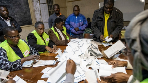 Ballot papers are poured onto a table in Harare as the counting of the votes begins during the Zimbabwean General Election