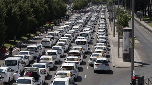 Taxi drivers with their vehicles block the Paseo de la Castellana Avenue in Madrid