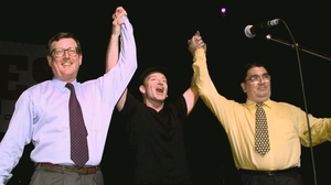Bono holds up the hands of David Trimble and John Hume during a concert in Belfast during the 1998 peace referendum