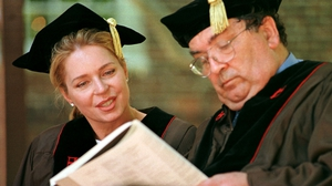 Queen Noor of Jordan checks the programme with Mr Hume at a ceremony in the US in 1999