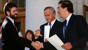 Gerry Adams and John Hume shake hands as Albert Reynolds looks on