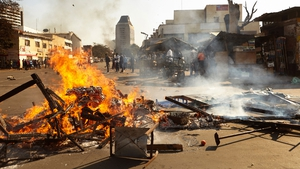 The wreckage of a market stall burns in Harare after protests erupted over alleged fraud in the country's elections