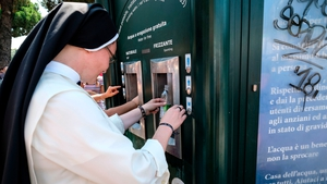 A nun takes water from a kiosk  in central Rome today as temperatures approach 40C