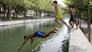 People jump into the Lis river to cool off in Leiria, central Portugal