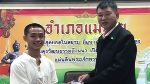 A member of the Wild Boar soccer team Adul Sam-on (L) receives his Thai citizen ID card from Mae Sai District Chief Somsak Kanakham