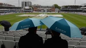 Spectators under umbrellas at Lord's