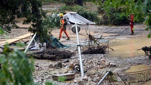 Rescue workers sift through the debris following the floods