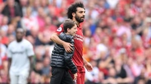 A young fan embraces Mo Salah during Liverpool's clash with West Ham at Anfield
