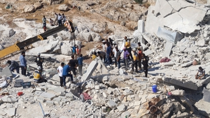 Syrian civil defence members conduct search and rescue operations at the wreckage in Idlib, Syria