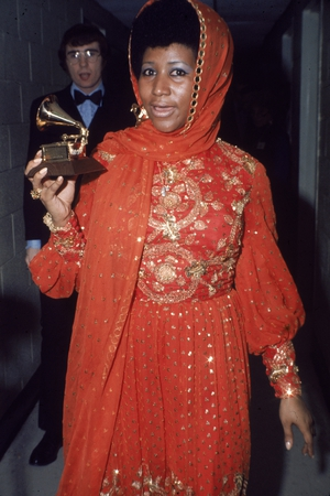 Aretha Franklin stands backstage wearing an gold embroidered gown and holding a Grammy Award, circa 1970. (Photo by Tim Boxer/Getty Images)