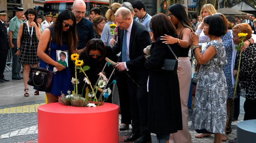 The family of one of the young victims of the attack - Julian Alessandro Cadman - plant flowers ahead of the ceremony