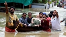 Indian people use a boat to rescue an elderly man in the flooded water in Kochi, Kerala state