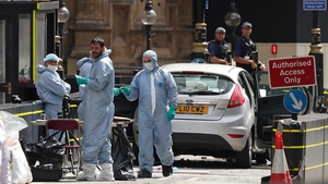 Forensics officers work around the silver Ford Fiesta car that was driven into a barrier at Westminster