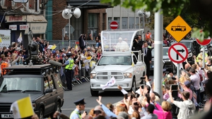 Pope Francis waves to the crowds on his way to the Capuchin Day Centre