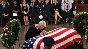 Cindy McCain, wife of John McCain, touches the casket during the ceremony