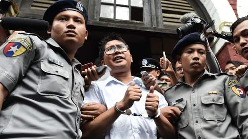 Journalist Wa Lone is escorted by police after being sentenced by a court to jail in Myanmar