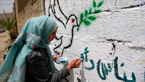 A Yemeni artist paints pro-peace graffiti on a wall in the capital Sanaa