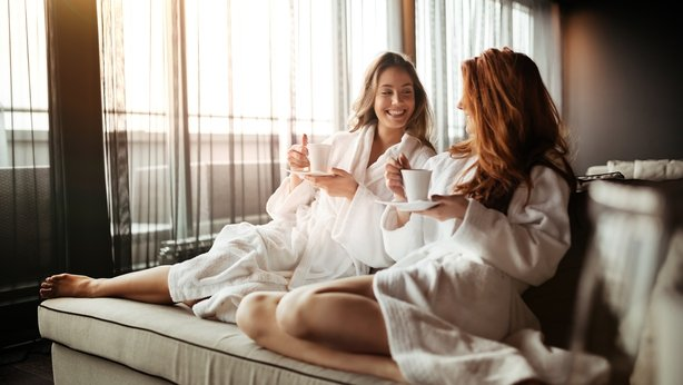 Women relaxing and drinking tea in robes during wellness weekend spa