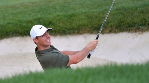 Rory McIlroy plays a shot from the ninth-hole bunker