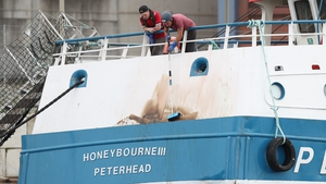 Members of the crew clean marks from the stern of the Honeybourne III, following clashes with French fishermen