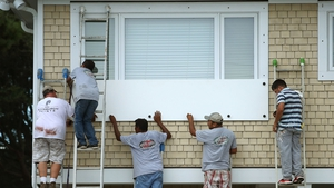Workers board up a home in the Wrightsville Beach area