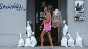 A women walks past a local shop that is preparing for the storm in North Carolina