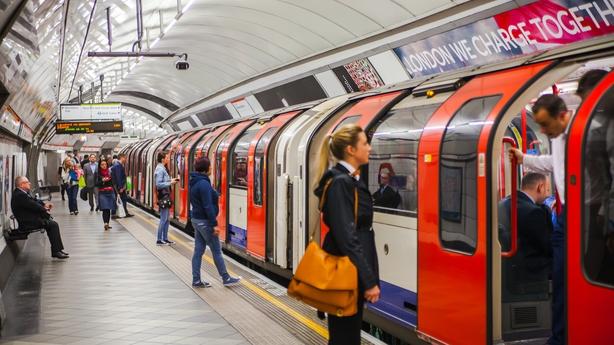 People waiting at underground tube platform for train arrives