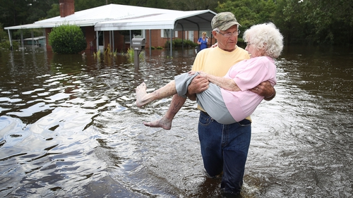 A woman is carried from her home in Spring Lake, North Carolina, as flood waters seep inside